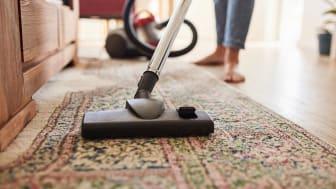 A woman vacuums a living room rug.