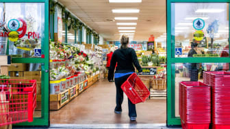 A shopper with a shopping basket enters the open doors of a Trader Joe's