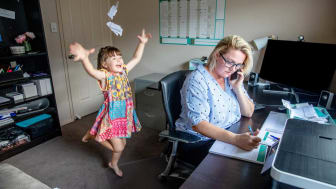 picture of woman trying to work from home while her daughter plays behind her