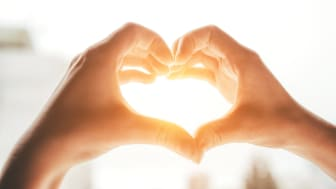 Two hands come together to form the shape of a heart