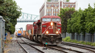 Montreal, Canada - June 30, 2011: Red Canadian Pacific freight train in downtown Montreal approaching the dockside area. A railway worker is checking one of the wagons