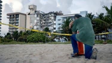 A man kneels with his head down in front of the collapsed condo building in Surfside, Florida.