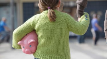 A little girl with a piggy bank under her arm holds her dad's hand.