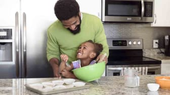 Small child learning to bake with her dad