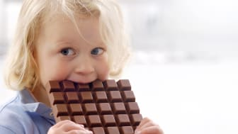 Portrait of little blond girl with huge chocolate bar
