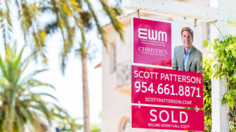 Closeup of red real estate agent sign on street during sunny day in Florida east coast in North Miami Beach with residential building and text for sold
