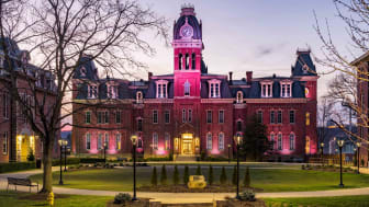 Dramatic image of Woodburn Hall at West Virginia University or WVU in Morgantown WV as the sun sets behind the illuminated historic building