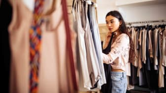 A woman looks through clothing