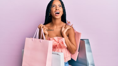 A woman holds many shopping bags and looks miffed.