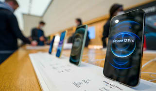 Apple iPhone 12 Pros are shown in an Apple store.