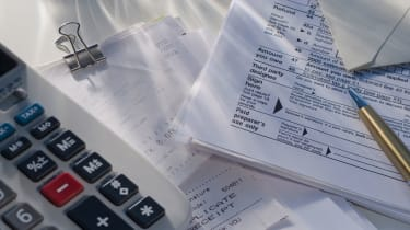 picture of tax forms, receipts, a calculator, and a pen
