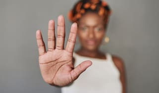 Woman holds up her hand to signal STOP.