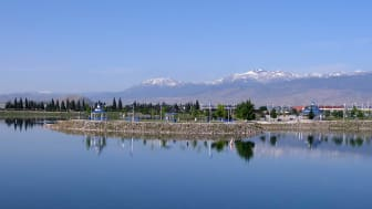A lake and gazebo with mountains in the background