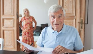 An older man looks up from papers with an enigmatic smile on his face as his wife stands in the background.
