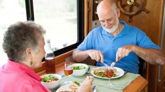 Senior couple eating dinner inside their RV