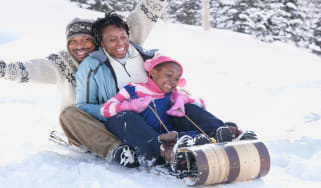 picture of mother, father and child sledding in the snow