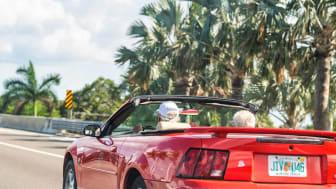 A senior couple riding in their convertible in Florida