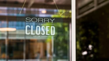 A sign reading Sorry, Closed hangs in a shop doorway