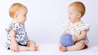 Two babies sit facing each other, one holding a ball and the other looking jealous.