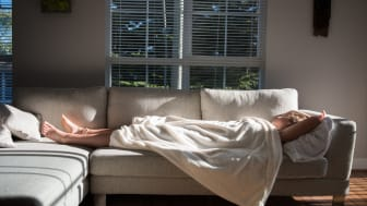 A woman sleeps on a sectional couch in the morning, the early morning summer sun lighting the room.