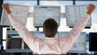 picture of investor looking at several computer screens and raising his arms up as if he has won