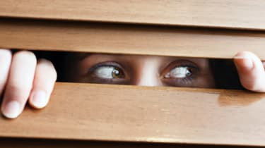 A tearful young woman with bloodshot eyes peers suspiciously to the side through the slats of a wooden venetian blind.
