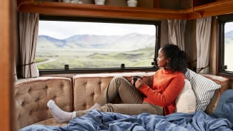 Contemplating woman with coffee cup sitting on bed in camper van