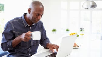 African American Man Using Laptop At Home In Kitchen