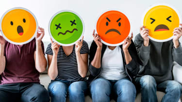 Four people holding up frustrated emoji faces.