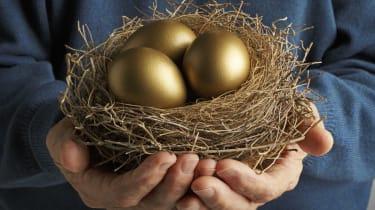 Senior Citizen holding three golden eggs in a bird's nest.