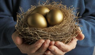 Senior Citizen holding three golden eggs in a bird's nest.