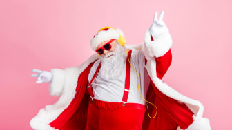 Funky Santa in sunglasses dances to holiday music through headphones