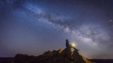 Man sitting under The Milky Way Galaxy with light on his hands.