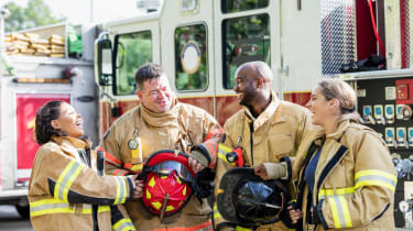 Four firefighters chat in front of a fire truck.