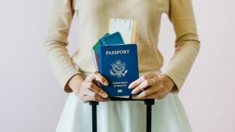picture of woman holding a U.S. passport and an airplane boarding pass
