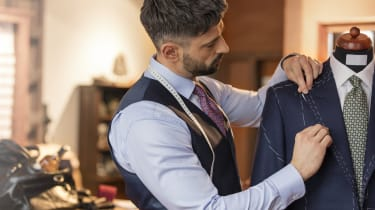 Tailor adjusting suit on dressmakers model in menswear shop