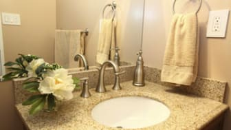 Modern bathroom vanity with beige granite top and faucets