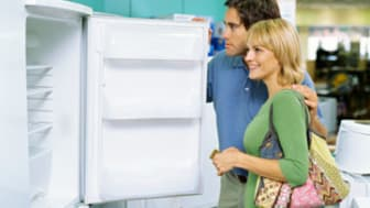 side profile of a young couple looking at an open refrigerator in an electronics store