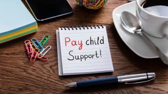 "picture of notebook with ""pay child support"" written on page"