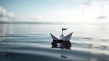 A paper boat sailing along a large body of water with subtle ripples