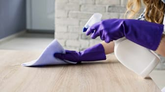 Gloved hands spraying and wiping down cleaner
