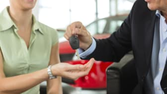 Woman hands car keys to man at auto dealer