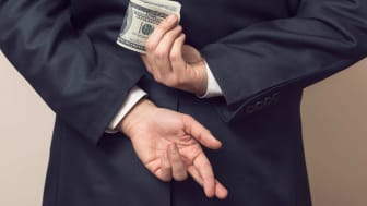 A man holds money behind his back and crosses his fingers.