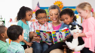 picture of young children gathered around a preschool teacher who is reading a book