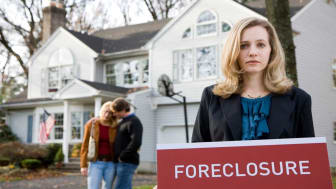 picture of a woman holding a foreclosure sign in front of a couple's house