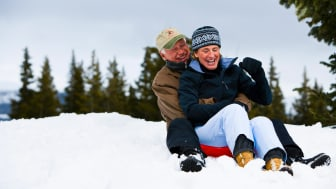 Senior couple sit on a sled in the snow on a Colorado mountain