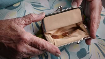 picture of elderly woman with a change purse that is nearly empty