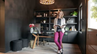 A woman stands in a well-designed office with an open design book