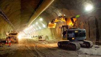 Heavy construction vehicles in a road tunnel being built.