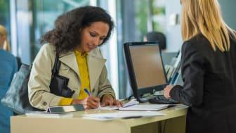 Woman filling form at bank counter.